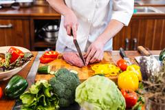 Professional chef cook cutting uncooked meat and fresh vegetables - stock photo