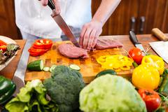 Chef cook cutting and preparing meat with fresh vegetables - stock photo