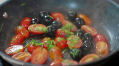 Frying vegetables pachino tomatoes and olives Stock Footage