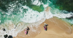 Aerial view of windsurfers launching into blue ocean from white sand beach - stock footage