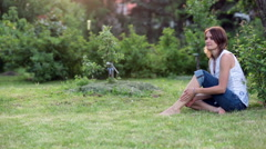 Young beautiful mother, sitting in a garden, little boy, her son, bringing ge Stock Footage