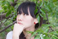 Asian girl standing amongst leaves - stock photo