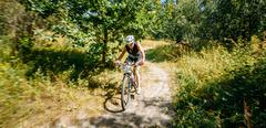 Young woman mountain Bike cyclist riding track in forest at sunn Stock Photos