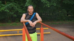 Portrait of a sportsman having a break after workout outdoors, young sporty guy Stock Footage