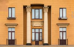 Windows in a row and balconies on facade of apartment building Stock Photos