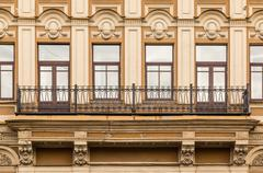 Windows in a row and balcony on facade of office building - stock photo