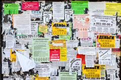 Dirty bulletin board filled with paper notices on russian language Stock Photos