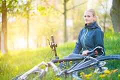 Young woman with bike in spring city at sunset - stock photo