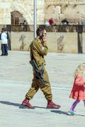 JERUSALEM, ISRAEL - FEBRUARY 17, 2013: Armed young soldier speaking mobile ph Stock Photos