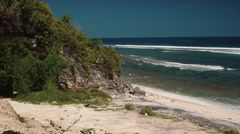 Empty clean white beach bordered by rocks with trees Stock Footage