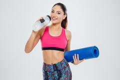 Happy woman holding yoga mat and drinking water - stock photo