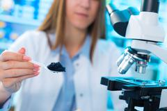 Quality control of food products. Young woman in chemical laboratory Stock Photos
