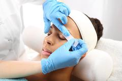 Hair removal, eyebrow regulation wax in the beauty salon . - stock photo