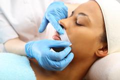 Depilation with hot wax mustache in the beauty salon . - stock photo