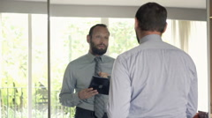 Young businessman with tablet trying his speech in front of mirror at home Stock Footage