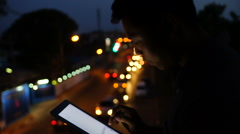 Handsome, young man with tablet computer in city at night - stock footage