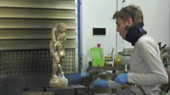 Laying a patina from titanium white on bronze Stock Footage