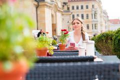 Woman drinking cappuccino at an outdoor cafe Stock Photos