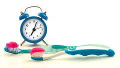 Composition from blue clock and toothbrushes with magenta toothpaste - stock photo