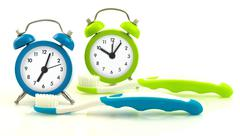 Composition from blue and green clocks and toothbrushes Stock Photos