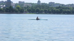 Single scull rowing competitor, water - stock footage