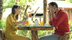 Young couple fighting, arguing during breakfast in cafe in garden Stock Footage
