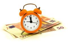 Alarm clock with paper money, 50 euro - stock photo