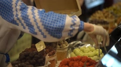 The seller in the candy store shop puts chocolates in a box - Lvov, Ukraine Stock Footage