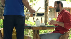 Young couple getting their order form waiter in cafe in garden  Stock Footage