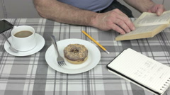 Man sitting at breakfast table reading book and drinking coffee - stock footage