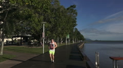 People walks and runs on Cairns Esplanade Queensland Australia Stock Footage