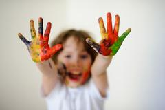 Child face and hands in the paint, he laughs - stock photo