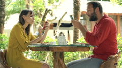 Young couple using smartphones sitting in cafe in garden  Stock Footage
