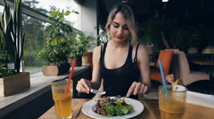 attractive woman in black dress in cafe eats salad - stock footage