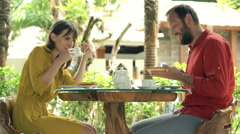 Young couple talking and eating breakfast sitting in cafe in garden  Stock Footage