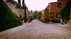 Slow motion steadicam of a cobble stone street with colorful houses and no cars Stock Footage