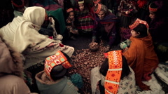 Elderly Woman from Kalash Tribe distributes Dry Nuts Stock Footage