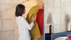 Angry woman trying to choose dress from wardrobe in room at home Stock Footage