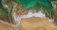 Aerial view waves break on white sand beach at sunset Stock Footage