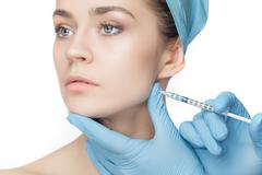 Attractive woman at plastic surgery with syringe in her face - stock photo