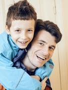 Young handsome father with his son fooling around at home, lifestyle people Stock Photos