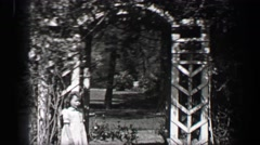 1939: Wealthy young girls play in white formal sundresses under arch garden Stock Footage