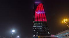 Wataniya Headquarters skyscraper illuminated at night downtown timelapse Stock Footage