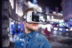 Man wearing virtual reality goggles. Night city - stock photo