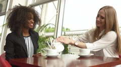 Two attractive mixed race businesswomen talking and making a deal while drinking Stock Footage