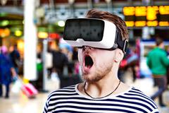 Man wearing virtual reality goggles standing at train station - stock photo