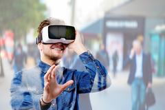 Man wearing virtual reality goggles. Crowded street of London Stock Photos