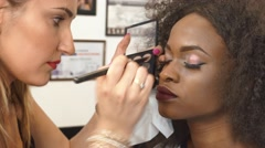 Makeup artist applying makeup on black african american eye lashes model. Pretty - stock footage