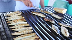 Chef preparing fish on a charcoal grill in food market at Eminonu, Istanbul Stock Footage
