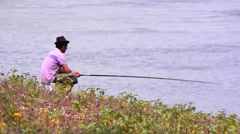 Man with pink shirt standing on the waterfront and fishing with rod Stock Footage